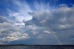 beaufitul云彩在下彩虹的colorfull湖 免版税图库摄影