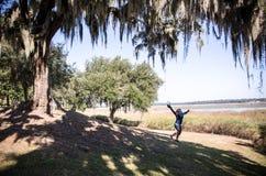 Beaufort South Carolina - spanisches Moos hängt im Vordergrund, während eine Frau in den Hintergrund springt stockbilder