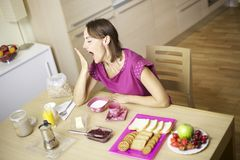 Beauitful female model yawning during breakfast Royalty Free Stock Photo