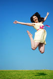 Beauitful girl jumping. A beautiful young woman jumping in a field with a blue sky royalty free stock photo