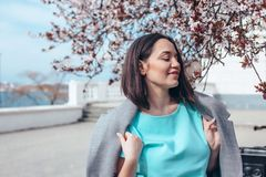 Beautiful model in blue dress and grey coat by spring blooming tree. Beauitful plus size model wearing blue dress and grey coat walking by blooming spring tree stock photography