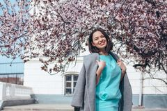 Beautiful model in blue dress and grey coat by spring blooming tree royalty free stock photos