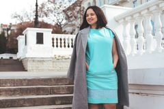 Beautiful model in blue dress and grey coat on city street royalty free stock photo