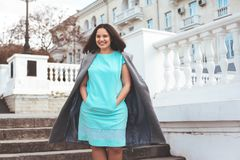 Beautiful model in blue dress and grey coat on city street stock image