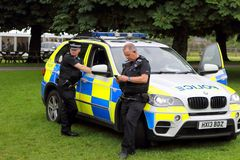 Beaulieu, Hampshire, UK - May 29 2017: Two British policemen taking a break with their BMW patrol car stock image