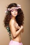 Beauté étouffante. Femme nue attirante avec le longs cheveu bouclé et guirlande des fleurs image libre de droits