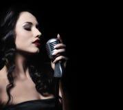 Beauté avec un microphone photo stock