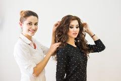 Beauté, coiffure et concept de personnes - jeune femme heureuse avec la coiffure de finissage de coiffeur au salon Image stock