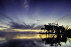 Beauté de silhouette et de réflexion sur l'eau pendant le lever de soleil de coucher du soleil à la plage avec les nuages mous et Photo libre de droits