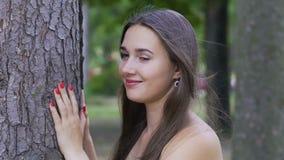 Beauté de sourire extérieure, brune femelle près de grand arbre, joie de la vie, bonheur banque de vidéos