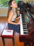 Beauté femelle asiatique jouant le piano image stock