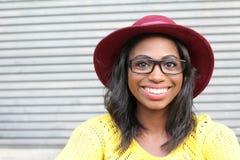 Beauté géniale de style Portrait de belle jeune femme africaine dans les verres et le sourire génial de chapeau photos libres de droits