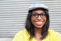 Beauté géniale de style Portrait de la belle jeune femme africaine dans les verres et le chapeau génial souriant tout en se tenan images stock