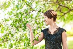 Beauté, les gens, été et concept de ressort - belle jeune femme au-dessus de fond de floraison vert de jardin photographie stock