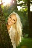 Beauté normale se cachant derrière un arbre Image libre de droits