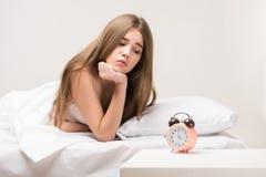 Beauté se trouvant sur le lit avec une horloge Photos libres de droits