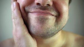 Beauté, toilettage et concept de personnes - jeune homme regardant au miroir et rasant la barbe avec le trimmer ou le rasoir élec banque de vidéos