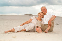 Beauteous elderly couple enjoy the sea breeze. Happy elderly couple went to the beach to enjoy the sea breeze Stock Photo
