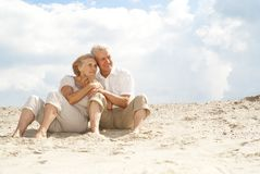 Beauteous elderly people enjoy the sea breeze. Attractive elderly couple went to the beach to enjoy the sea breeze Royalty Free Stock Photography