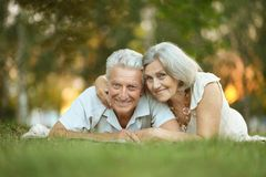 Beauteous old couple. Lying on the grass Royalty Free Stock Photos