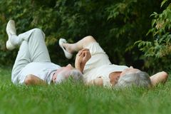 Beauteous old couple. Lying on the grass Stock Photo