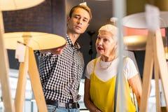 Beauteous oud mevrouw en aantrekkelijke rijpe mens die nadenken kopend standaard-lampen royalty-vrije stock afbeelding
