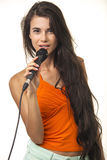 Beauteous woman in orange shirt with microphone. Lovely brunette with long hair is holding microphone on the white background. Beauteous woman in orange shirt Stock Photos