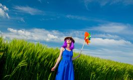 Purple hair girl with pinwheel at wheat field Royalty Free Stock Photography