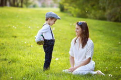 Beautful kid and mom in spring park, flower and present Stock Photography