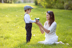 Beautful kid and mom in spring park, flower and present Royalty Free Stock Images