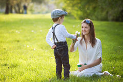 Beautful kid and mom in spring park, flower and present. Mothers Stock Photo