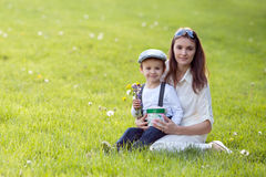 Beautful kid and mom in spring park, flower and present. Mothers Stock Photography