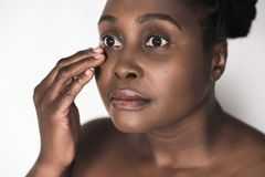 Beautful young African woman feeling the skin around her eyes. Young plus size African woman with a perfect complexion touching the skin around her eye while Royalty Free Stock Photos