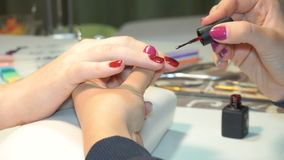Beautician που εφαρμόζει τα πολωνικά καρφιά στα καρφιά γυναικών απόθεμα βίντεο