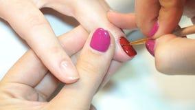 Beautician που εφαρμόζει τα πολωνικά καρφιά στα καρφιά γυναικών φιλμ μικρού μήκους