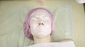 Beautician που εφαρμόζει την του προσώπου μάσκα σε ένα πρόσωπο γυναικών, που καθαρίζει την επεξεργασία δερμάτων φιλμ μικρού μήκους