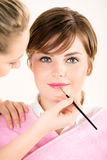 Beautician που ισχύει lipgloss για μια νέα γυναίκα Στοκ φωτογραφία με δικαίωμα ελεύθερης χρήσης