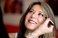 Beautician που ισχύει makeup για μια νέα γυναίκα Στοκ Φωτογραφία