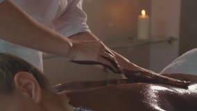 Beautician που κάνει το μασάζ με τη σοκολάτα στη νέα όμορφη γυναίκα στο σαλόνι SPA απόθεμα βίντεο