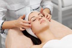 Beautician που κάνει το μασάζ προσώπου στο όμορφο brunette Στοκ φωτογραφία με δικαίωμα ελεύθερης χρήσης