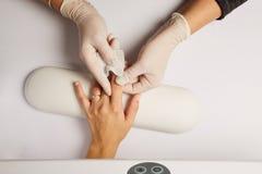 Beautician στο άσπρο ασβεστοκονίαμα κόλλας γαντιών στο δάχτυλο Στοκ Εικόνες