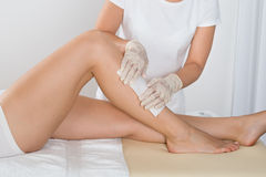 Beautician вощия ногу женщины Стоковая Фотография