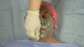 Beautician в перчатках прикладывает терапевтическую маску глины к стороне человека s с щеткой Подолы времени сток-видео