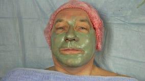 Beautician в перчатках прикладывает терапевтическую маску глины к стороне man's с щеткой акции видеоматериалы