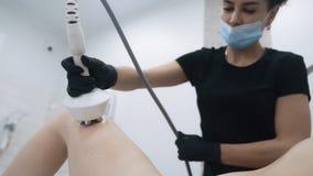 Beautician делает анти- процедуру по целлюлита на терпеливых ногах на клинике, замедленном движении акции видеоматериалы