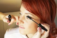 beautician делая девушку с волосами делает красный цвет к вверх стоковое фото