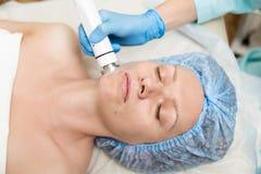 Beautician делает RF-подниматься к молодой женщине Косметические процедуры для стороны Косметики в салоне курорта Стоковое фото RF