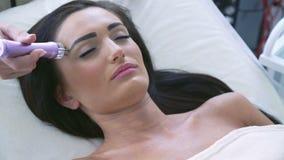 Beautician делая возбуждающий лицевой массаж с процедурой по оборудования сток-видео