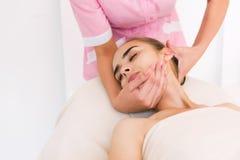 Beautician делая массаж женских сторон Стоковое фото RF