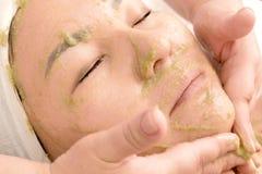 Beautician кладет зеленую маску на сторону азиатских девушек Конец-вверх стороны женщины с маской семян кивиа cosmetology beatnik стоковое фото
